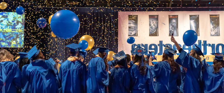 Blue and gold balloons and confetti surround graduates wearing blue caps and gowns at Commencement