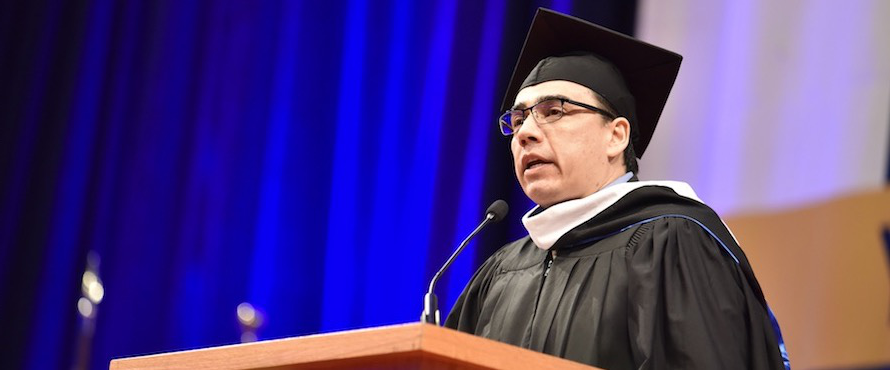 Alumnus Michael Orona addresses the graduates at the December 2019 Commencement ceremony