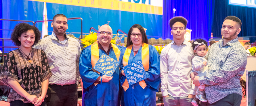 Photo of Ruby and Joel Rodriguez (center) surrounded by their children and grandchild at NEIU's December 2019 Commencement