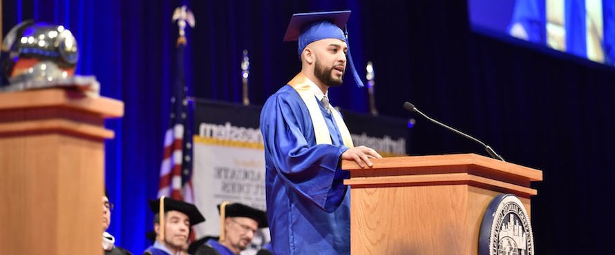 Michael Angelo Ortega delivers the student speech during Commencement while wearing a blue cap and gown.