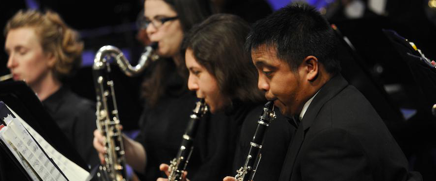 Four members of the Wind Ensemble play their instruments on stage.
