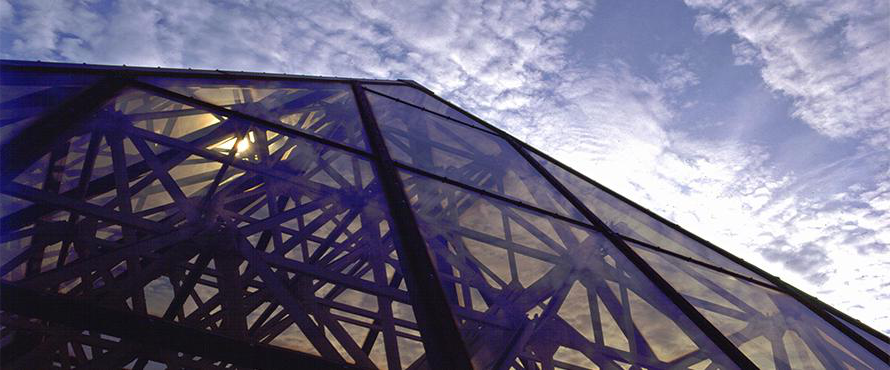 A glass roof is shown in front of a blue sky.