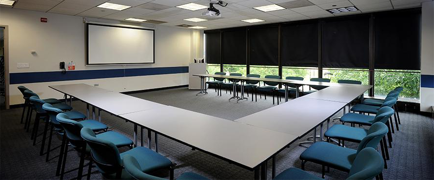 An empty conference room with a table and chairs.