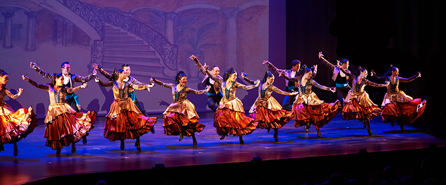 A line of Ensemble Español dancers performs on stage.