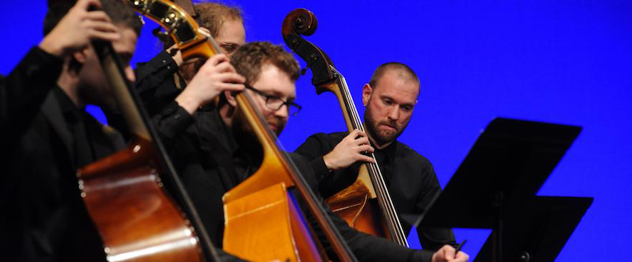 Four musicians perform on stringed instruments.